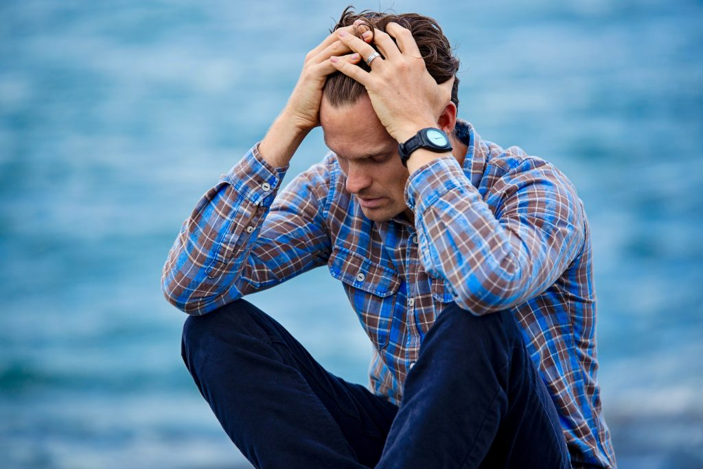 man sitting on ground confused in plaid shirt and jeans